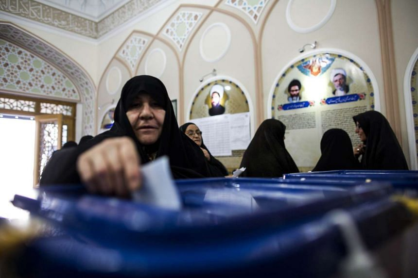An Iranian woman casts her ballot to vote at a polling station in Qom.