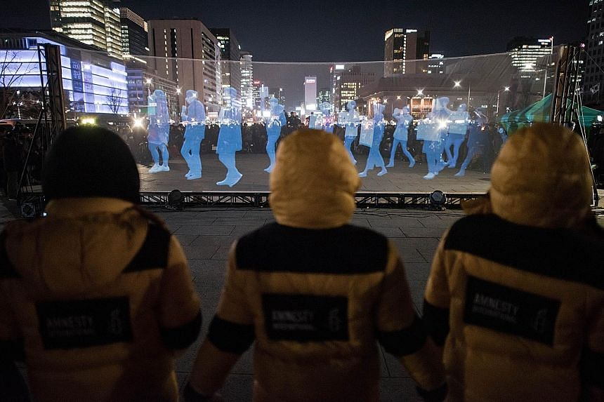 """A screen displaying """"ghost protesters"""" during a rally by Amnesty International in support of freedom of assembly and expression in South Korea. The human rights group pushed ahead with the """"Ghost Protest"""" after police threatened a crackdown on the vi"""