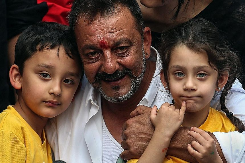 Mr Dutt hugging his twins Shahraan (far left) and Iqra. He was jailed for possessing an automatic rifle and a pistol that were part of a cache of weapons brought to Mumbai before the 1993 bombings which killed 257 people.