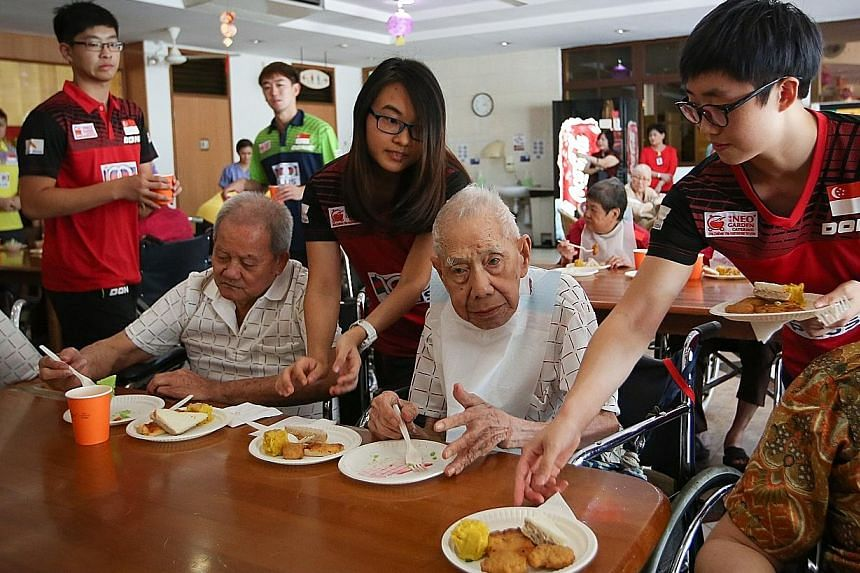 Singapore's women's table tennis players Feng Tianwei (right) and Isabelle Li serving food to elderly residents at the Man Fut Tong Nursing Home on the team's visit there yesterday. The women have set themselves a target to win a medal at the World T