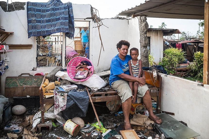 A woman and her son in their damaged house in Viti Levu on Wednesday. The death toll from Cyclone Winston so far is 44. Officials at Fiji's National Disaster Management Office fear that the figure will rise.