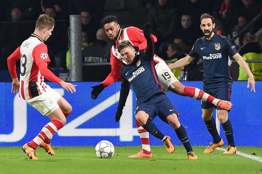 Atletico Madrid's forward Luciano Vietto (centre) fights for the ball against PSV's midfielder Marco van Ginkel (left) and forward Jurgen Locadia (back).