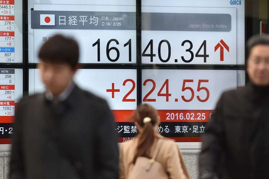 People walking past an electric share prices board in Tokyo on Feb 25.