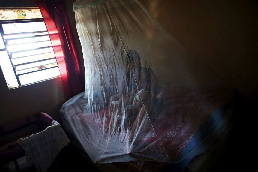 Vanessa, 32, feeds her daughter Valentina who is 5-months old and born with microcephaly, with a bottle under a mosquito net, inside their house in Jaboatao, near Recife, Brazil, on Feb 12, 2016.