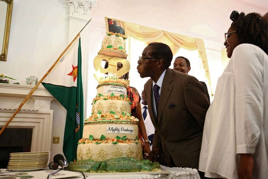 Robert Mugabe blows out the candles on his birthday cake at the state house in Harare, Zimbabwe, on Feb 22, 2016.