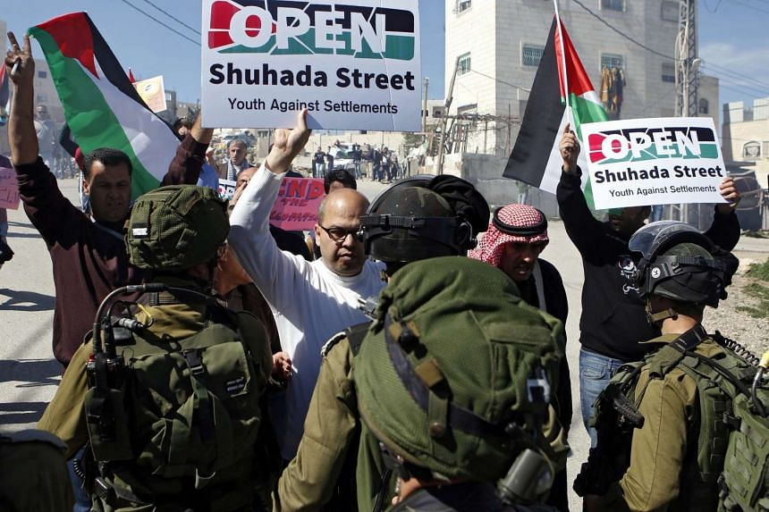 Palestinian protesters hold placards during a demonstration at Kiryat Arba settlement near the West Bank City of Hebron, on Feb 26, 2016.