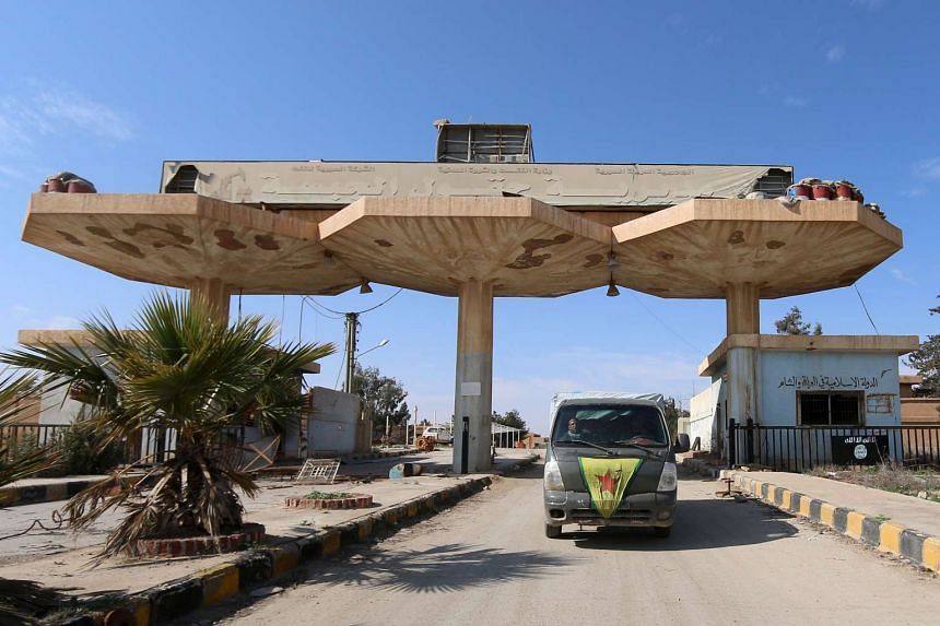 A vehicle that belongs to the Democratic Forces of Syria drives along a street in Hasaka province, Syria.