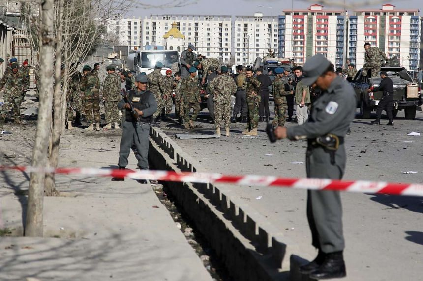 Afghan security officials secure the site of a suicide bomb blast near the defence ministry in Kabul.