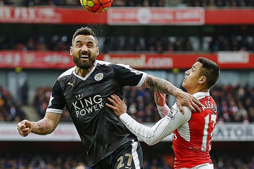 Leicester's Marcin Wasilewski beating Arsenal's Alexis Sanchez to the ball in their 1-2 loss. Despite the setback, the Foxes lead by two points and will be in pole position for the title run-in if they win the next five games.