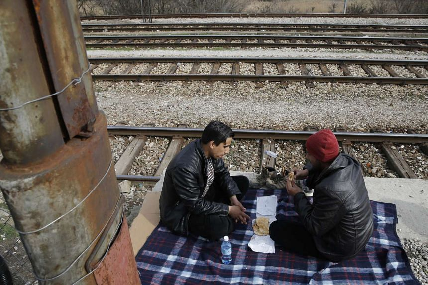 Migrants from Afghanistan eating inside a camp near the Macedonian-Serbian border at a train station on Feb 26, 2016.