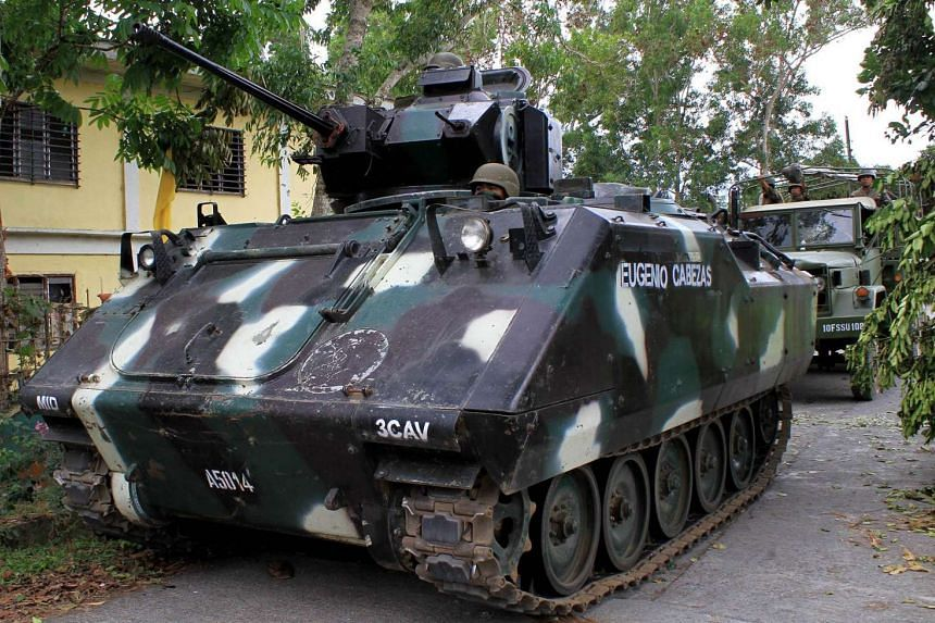 An armoured tank waits near the town hall in Butig Town, Lanao Del Sur, Mindanao on Feb 26, 2016, after a military operation in the area.