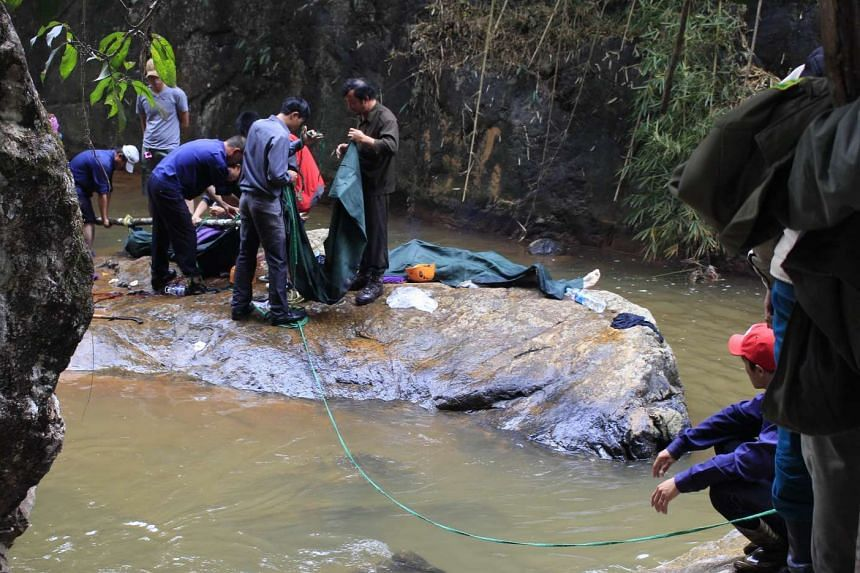 Rescuers preparing to carry two bodies of British tourists near a waterfall on the outskirts of the central highland town of Dalat on Feb 26, 2016.