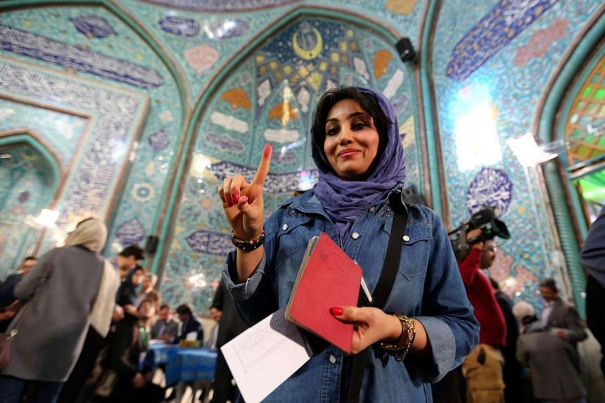 An Iranian woman shows her inked finger after casting her ballot at a polling station in Teheran on Feb 26, 2016.