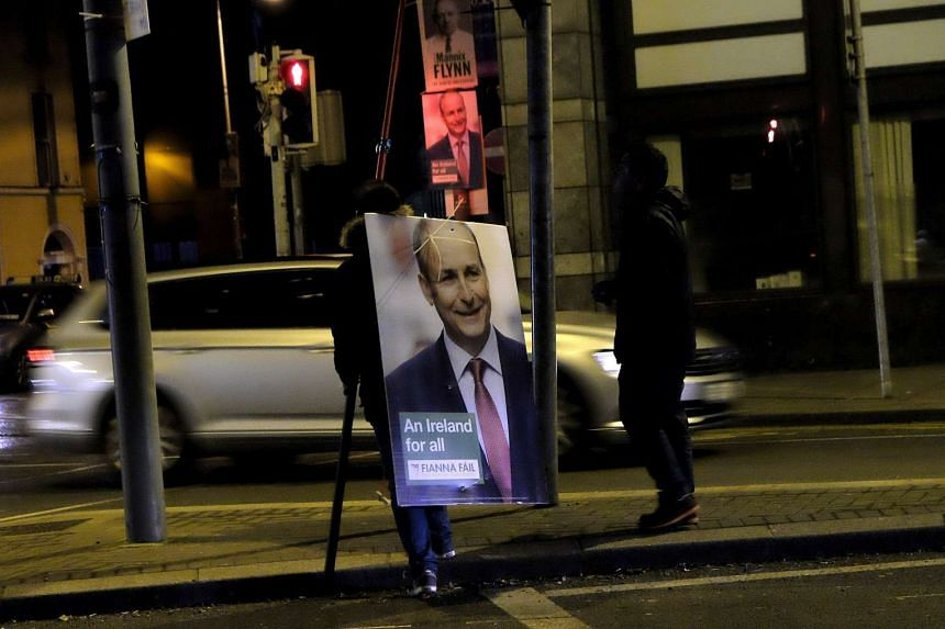 A man removing a campaign poster for Fianna Fail leader Micheal Martin after polling stations closed in Dublin, Ireland on Feb 26, 2016.