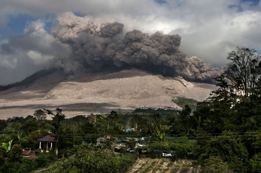 Mount Sinabung spewing volcanic ash, seen from Gamber village in Karo district, in North Sumatra yesterday. It is one of 129 active volcanoes in Indonesia. The country sits on the Pacific Ring of Fire, a belt of seismic activity running around the basin o