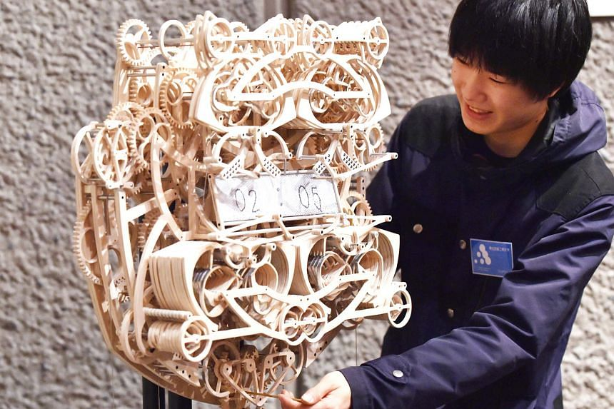 Japan's Tohoku University of Art and Design student Suzuki Kango, 22, with his wooden clock at the Tokyo Metropolitan Art Museum. The 407-piece clock took him six months to build and is set into motion by a series of weights. It writes the time on a