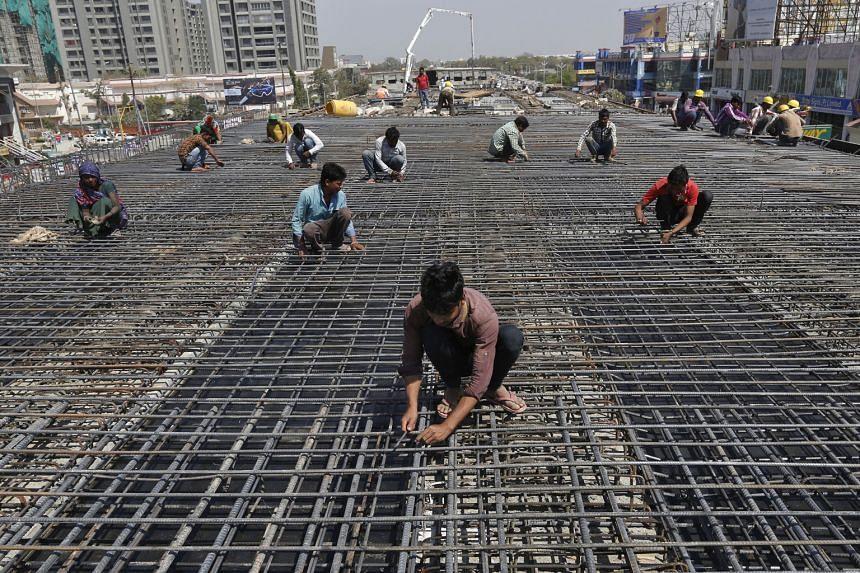 Workers at a flyover construction site on the outskirts of Ahmedabad in western India. Prime Minister Narendra Modi has made economic growth a priority, but investors have raised concerns about the pace of reform.