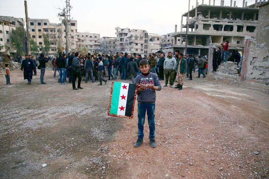 A boy carries an opposition flag in the rebel-held town of Kafr Batna. The Syrian Observatory for Human Rights said Russia and the regime yesterday launched a wave of attacks on rebel areas ahead of the ceasefire deadline.
