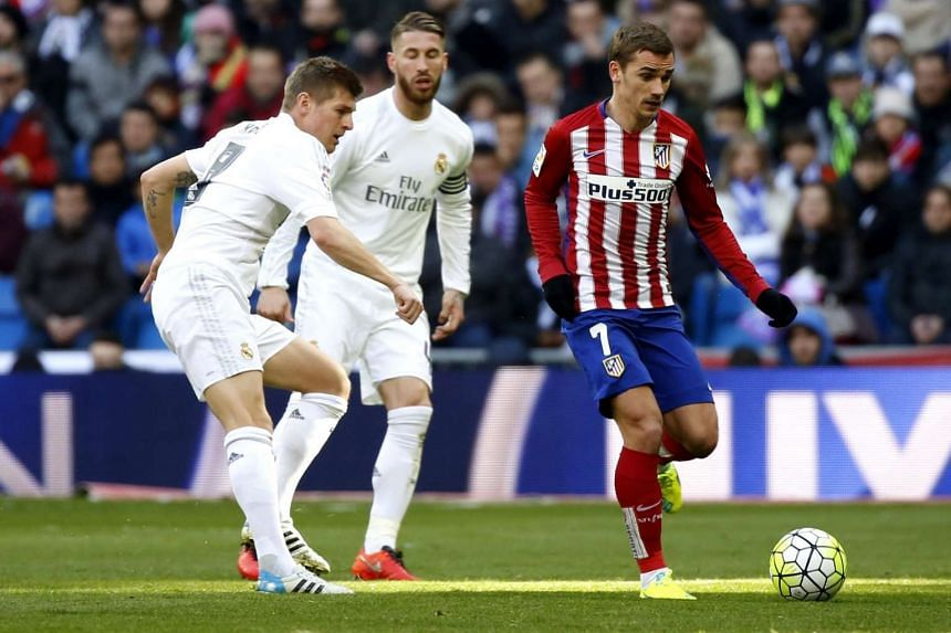 Real Madrid's German midfielder Toni Kroos (left) duels for the ball with Atletico Madrid's French midfielder Antoine Griezmann (right) during the Spanish Liga Primera Division soccer match played at Santiago Bernabeu stadium in Madrid, Spain, on Feb