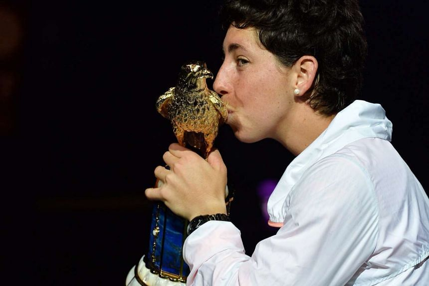 Carla Suarez Navarro of Spain poses with her trophy after beating her opponent Jelena Ostapenko of Latvia during their final match of the WTA Qatar Ladies Open at the International Khalifa Tennis Complex Doha, Qatar on Feb 27, 2016
