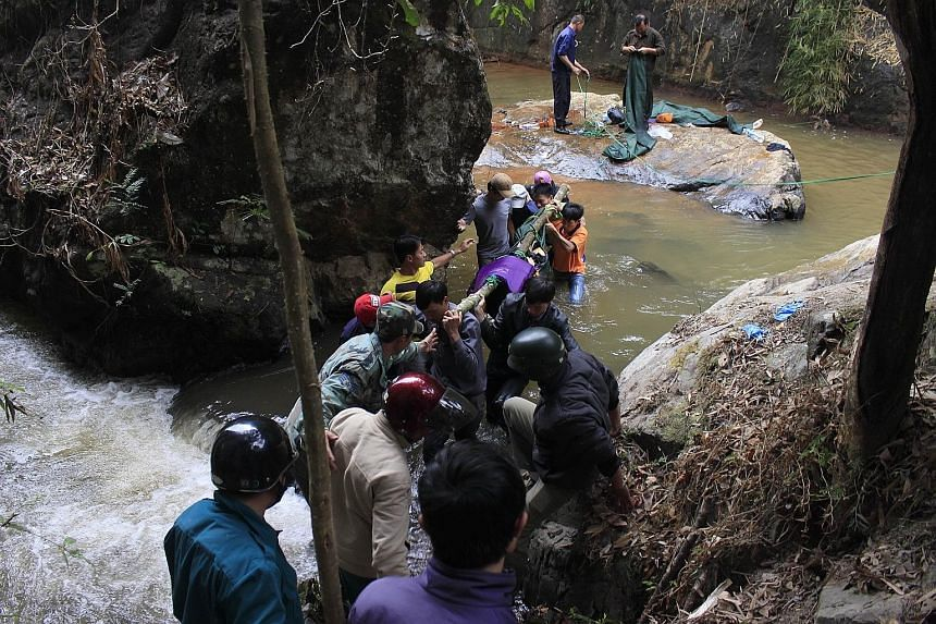Rescuers with the body of one of three British tourists who died after falling into a waterfall on the outskirts of the central highland town of Dalat in Vietnam on Friday. It is believed that one of them slipped and inadvertently dragged the others
