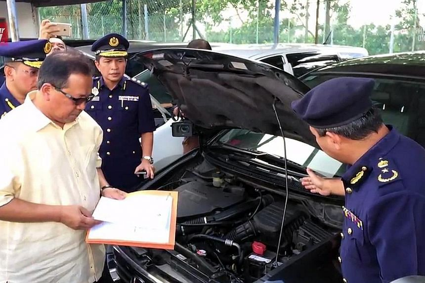 """Datuk Seri Ismail Ahmad, director-general of Malaysia's Road Transport Department, last Friday inspecting """"cloned"""" cars brought in from Singapore, which were later given new chassis numbers and sold in Malaysia."""