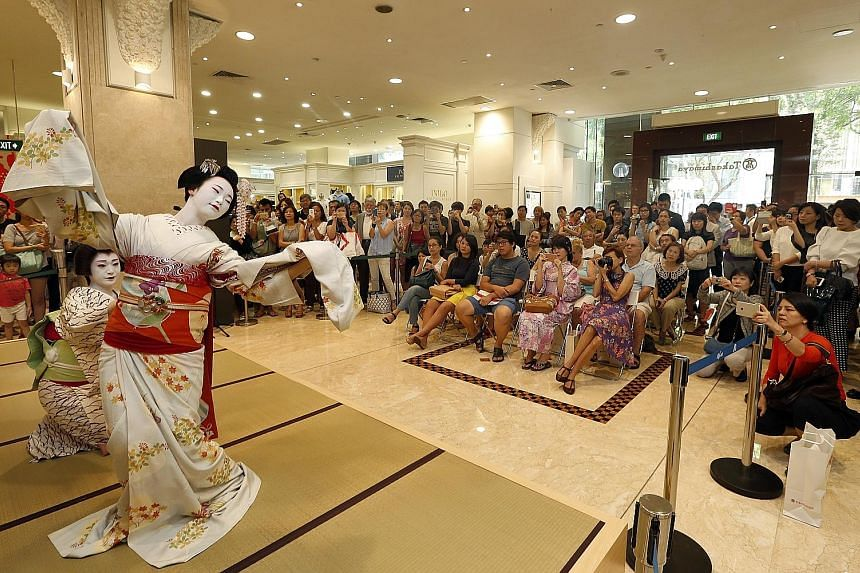 Performers from Kyoto doing a traditional duet dance for shoppers at Takashimaya department store yesterday, as part of the Kyoto Sakura celebration. The dancers are known as geiko (far left) and maiko - as geishas are known in Kyoto. The maiko is an