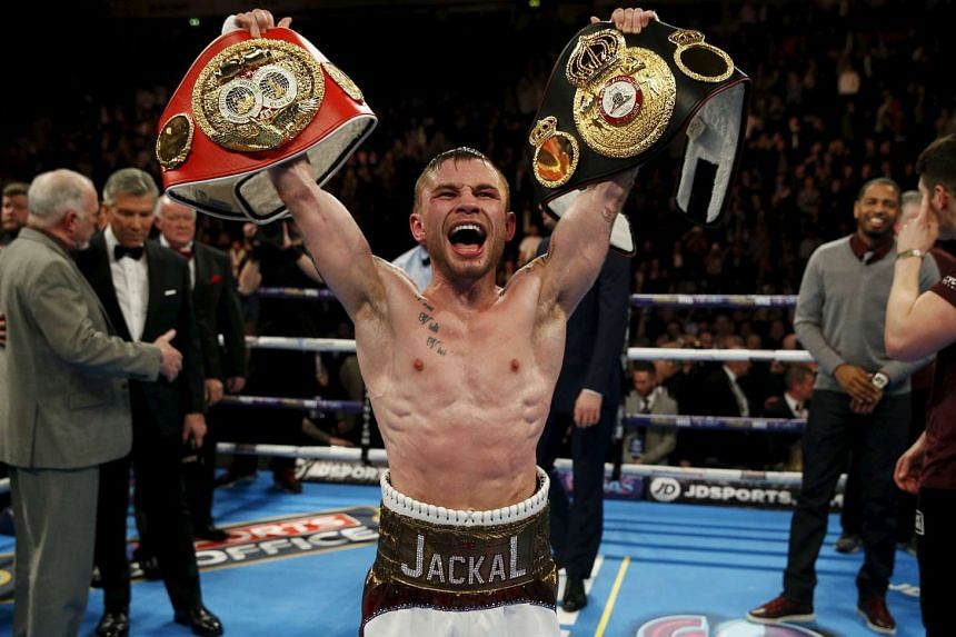 Carl Frampton celebrates winning the fight against Scott Quigg with the belt.