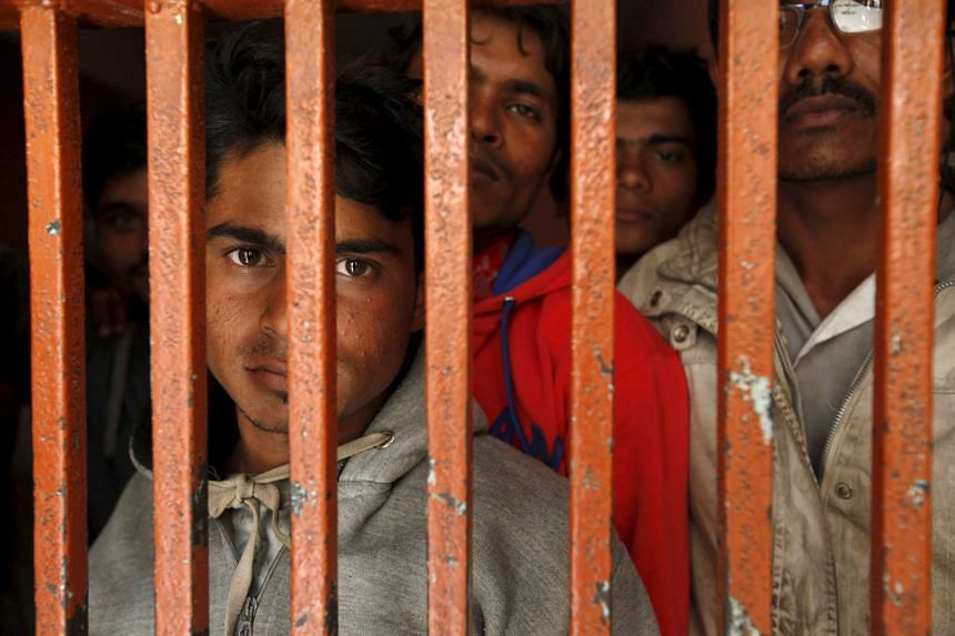 Fishermen from India look on from behind the bars of lockup cell at a police station in Karachi, Pakistan, on Feb 20, 2016.