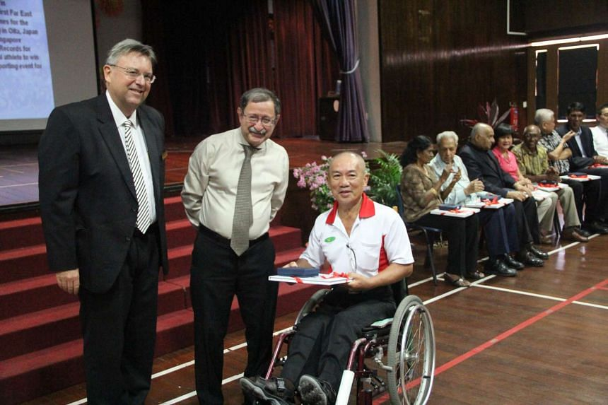 Dr Matthew Sullivan (left) and Mr Mirza Namazie (centre) giving a copy of the book to former Singapore para athlete Robert Tan.