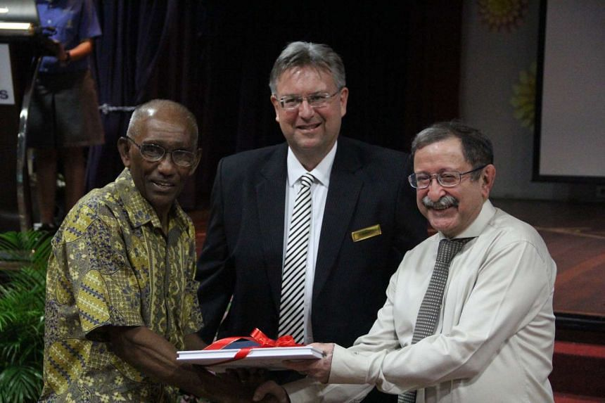 Former national sprinter C. Kunalan (left) receiving a copy of the book from NPSI head Matthew Sullivan and Mr Mirza Namazie.