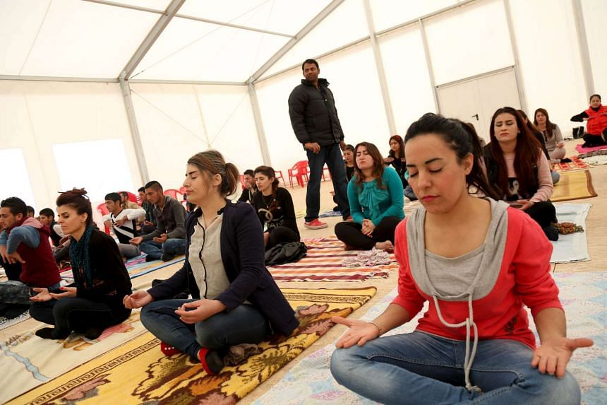 Displaced Yazidi women practising yoga at a refugee camp on the outskirts of Dukok province.