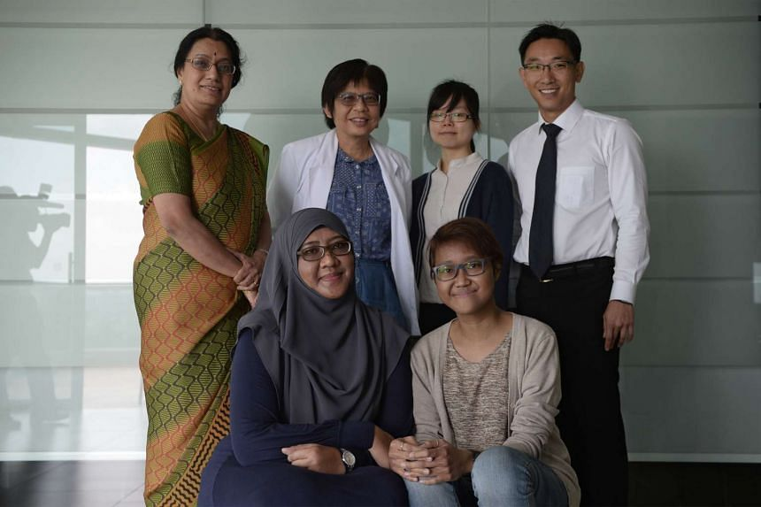 Ms Siti Rasyidah Lokman Hadan (front, right), her mother Noor Rafidah Nasir (front left) and the team behind Singapore's first living paired kidney exchange transplant.