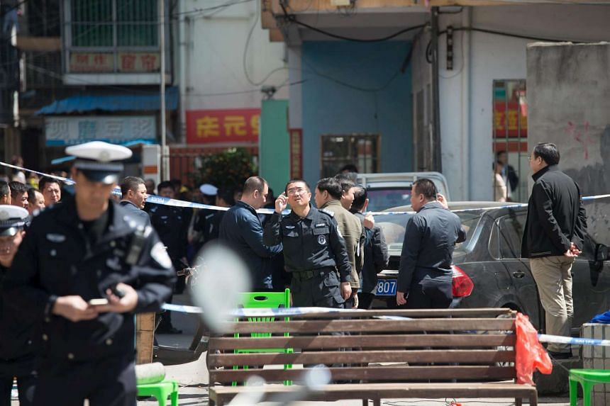 Police officers cordoning off an area outside an elementary school where 10 children were stabbed, in Haikou, Hainan province, on Feb 29, 2016.
