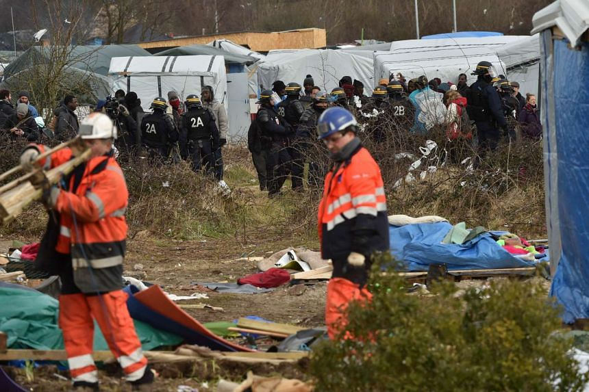 """Agents dismantle a shelter as anti-riot policemen stand nearby on Feb 29, 2016 in the """"jungle"""" migrants and refugees camp in Calais."""