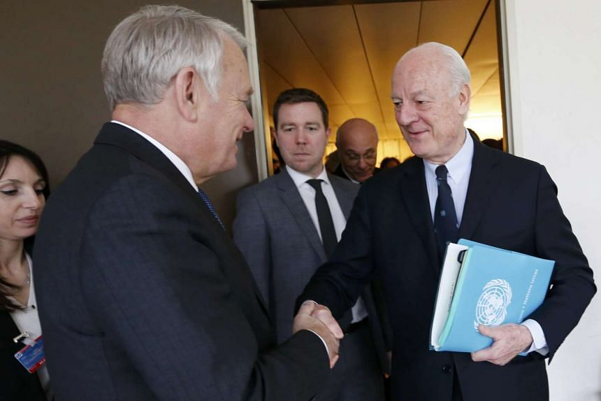 French Foreign Minister Jean-Marc Ayrault (left) shakes hands with United Nations Special Envoy for Syria Staffan de Mistura at the UN European headquarters in Geneva on Feb 29, 2016.