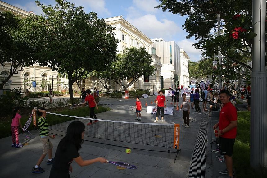 Participants enjoying a modified version of tennis in front of the Victoria Theatre and Concert Hall yesterday morning. They were also able to try out modified versions of sports such as basketball and football. A piloxing fitness party at the Empres