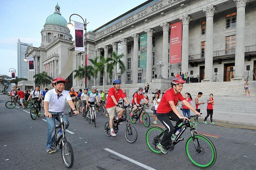 Left: Cycling past the National Gallery Singapore along St Andrew's Road are Coordinating Minister for Infrastructure and Minister for Transport Khaw Boon Wan (left) and Mr Lawrence Wong (right).