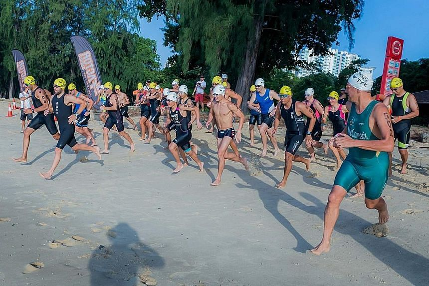 Two-time Ironman world champion Chris McCormack (in green suit) joining 46 participants for an aquathlon race to finish off a three-day training camp at East Coast Park yesterday. McCormack was in town to launch the TRI-Factor triathlon series.