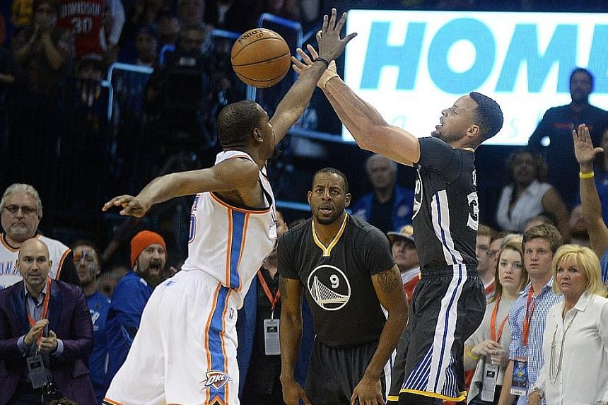 Golden State Warriors guard Stephen Curry (right) attempting a three-point shot against Oklahoma City Thunder forward Kevin Durant during the fourth quarter of their NBA game on Saturday. Curry finished with 12 three-pointers, tying the NBA single-ga