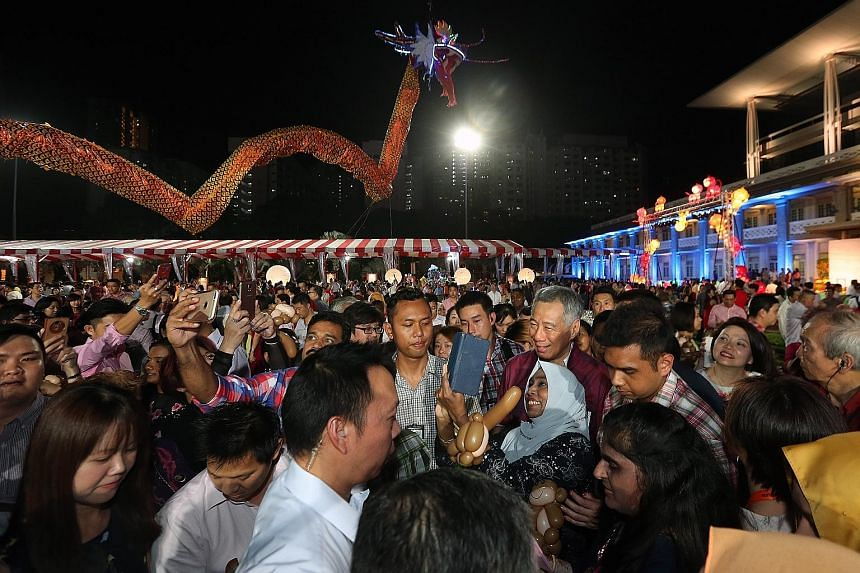 Some of the guests whipping out their mobile phones in hopes of taking a selfie with PM Lee Hsien Loong at the garden party held at the People's Association headquarters last night to thank grassroots leaders for their contributions.
