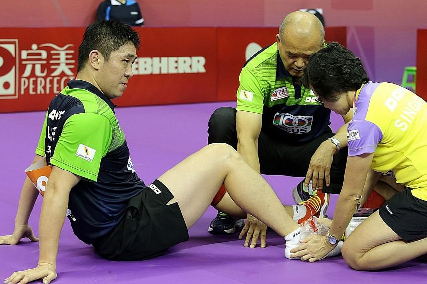 Gao Ning receiving treatment after spraining his ankle yesterday. The Singaporean returned to the table after 10 minutes but lost to Poland's world No. 82 Jakub Dyjas in the first singles. He later bounced back to beat Wang Zengyi in the fourth singl