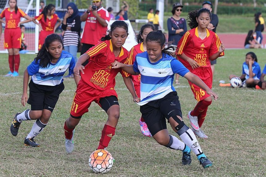 Furious action during a tournament for girls at the Women's Football Day in Kallang yesterday.