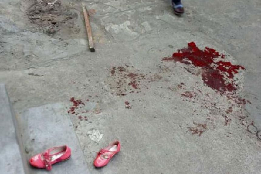Bloodstains are seen outside an elementary school in Haikou, after a man attacked several children there before killing himself.