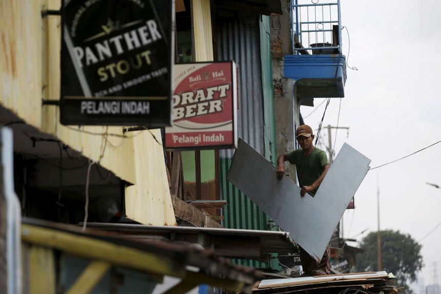 A man removing scrap building material from a former entertainment spot before the area is to be demolished in Kalijodo red-light district in Jakarta, Indonesia on Feb 26, 2016.