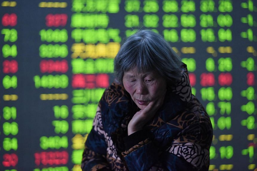 An investor stands in front of an electronic board showing stock information at a brokerage house, in Hangzhou, on Feb 25, 2016.
