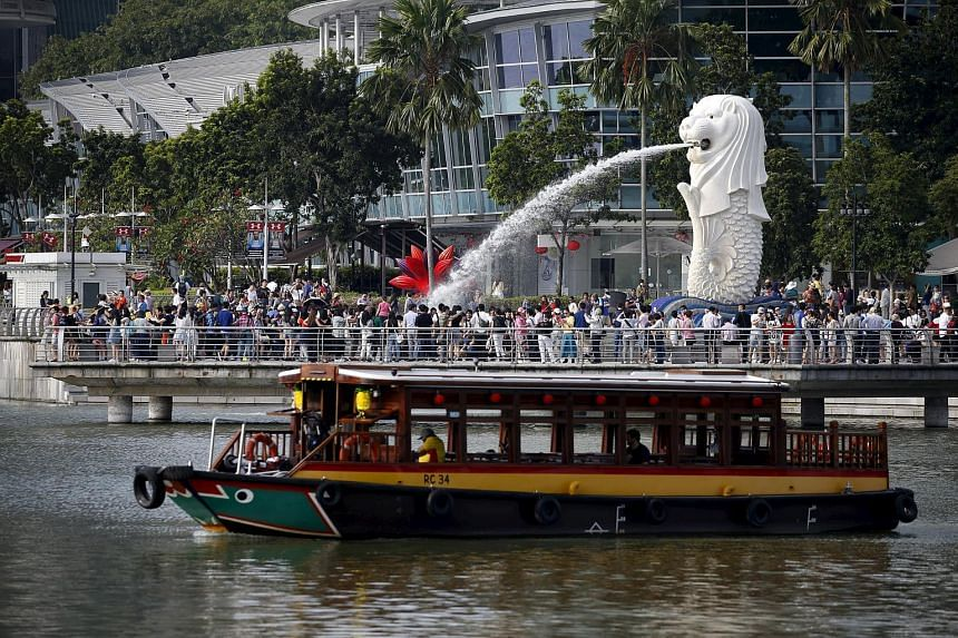 A bumboat passes tourists at the Singapore Merlion Park, on Feb 22, 2016.