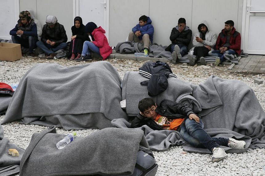 Migrants rest as they wait for a train inside a camp after crossing the Macedonian-Greek border in Gevgelija, Macedonia, on Feb 26, 2016.