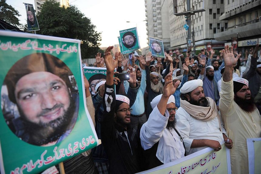 Pakistani supporters of former police bodyguard Mumtaz Qadri carry placards of his portrait during a protest in Karachi, on Dec 14, 2015.