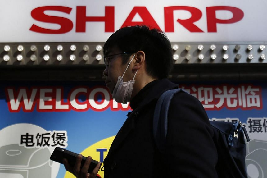 A pedestrian holding his mobile phone walks under a logo of Sharp Corp in Tokyo, Japan, on Feb 26, 2016.